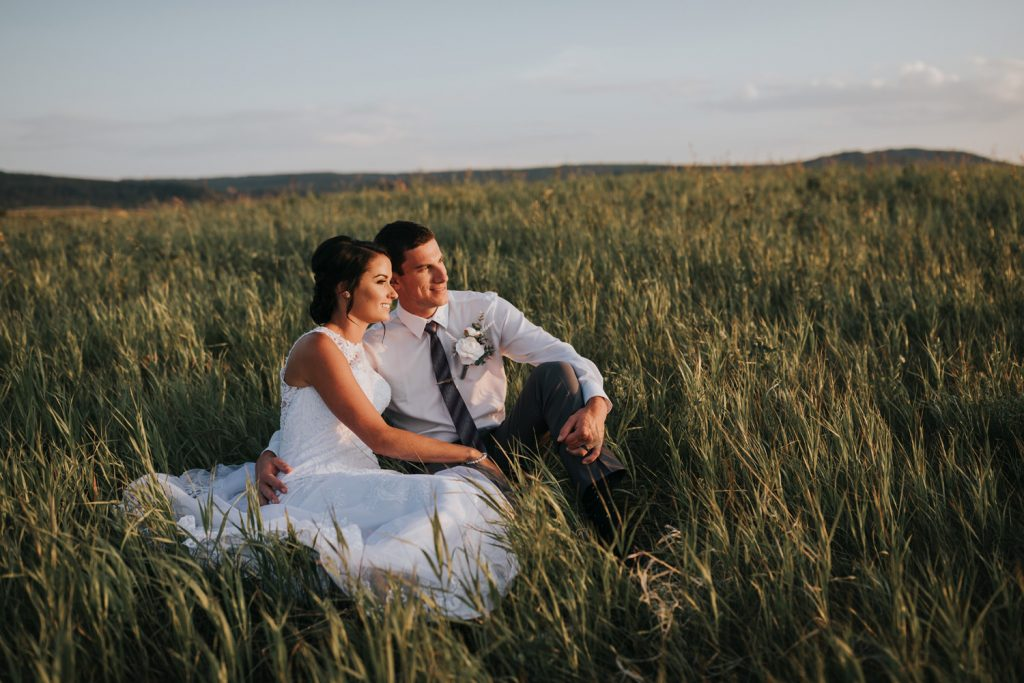 happy couple sits in tall grass watching the sunset in cypress hills alberta