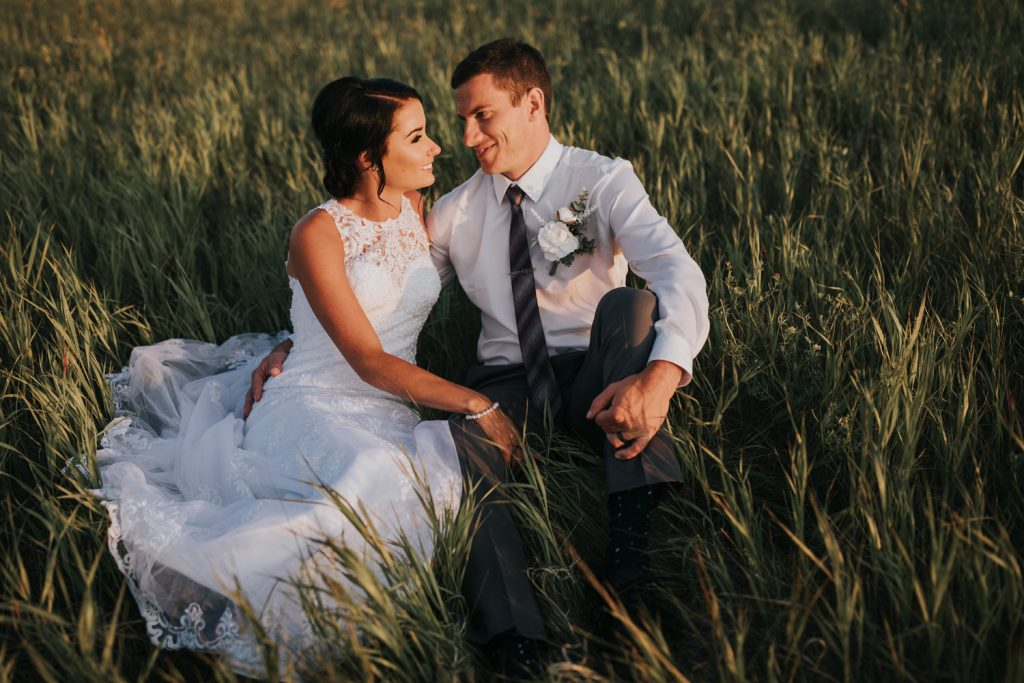 wedding couple sitting in tall grassy field smiling