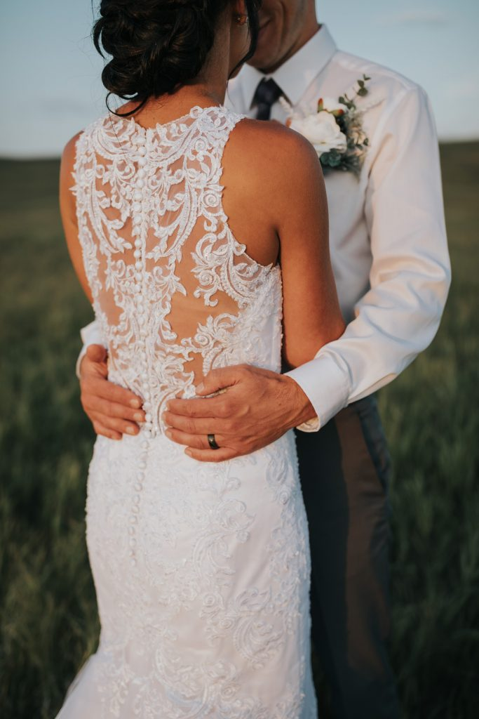 photo of groom's ring as his hands are wrapped around bride's waist