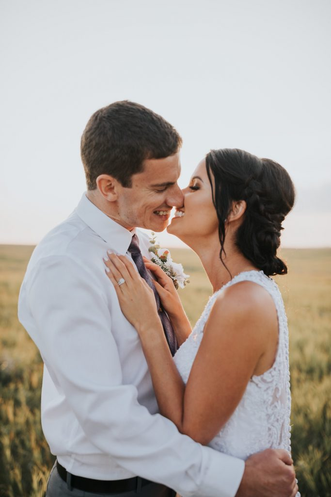 bride and groom smiling as they lean in for a kiss