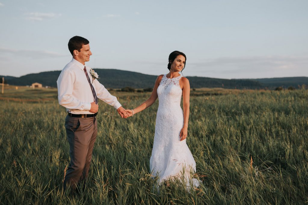 groom looks lovingly at bride while they hold hands