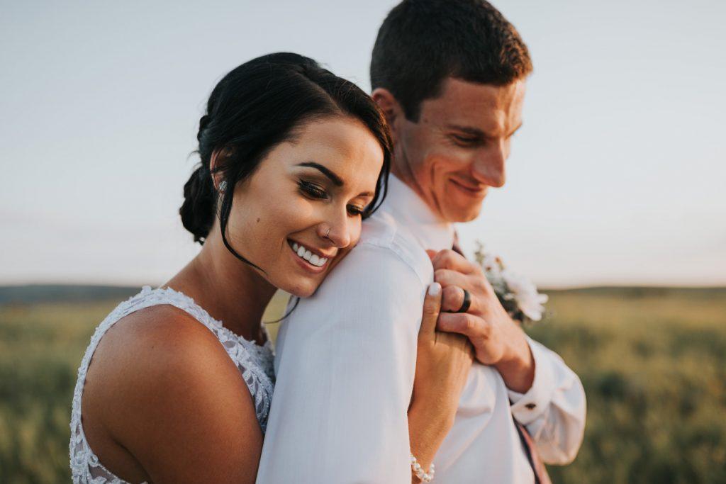bride cuddles groom from behind smiling