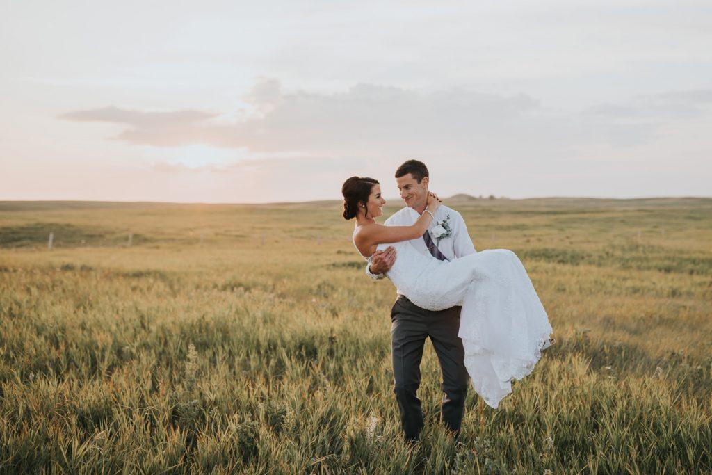 groom carrying happy bride at sunset elkwater alberta