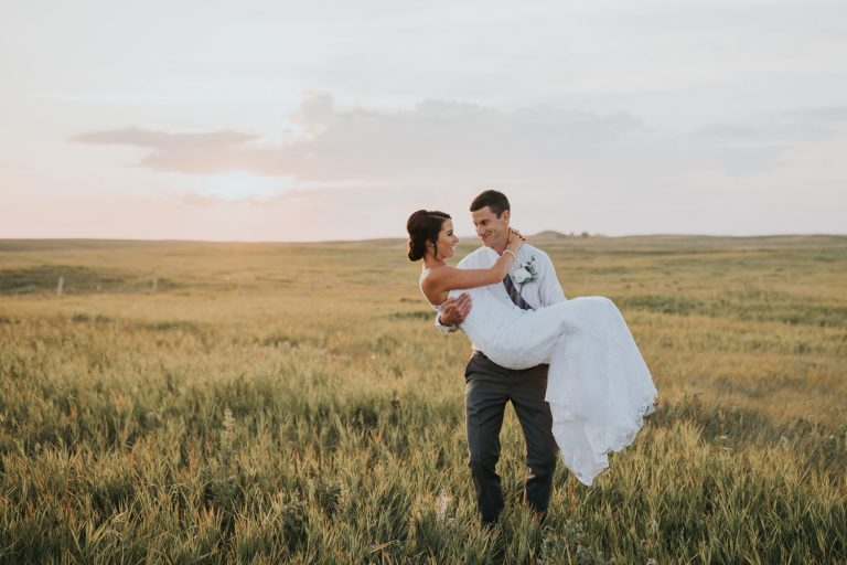 groom carrying happy bride at sunset elkwater alberta