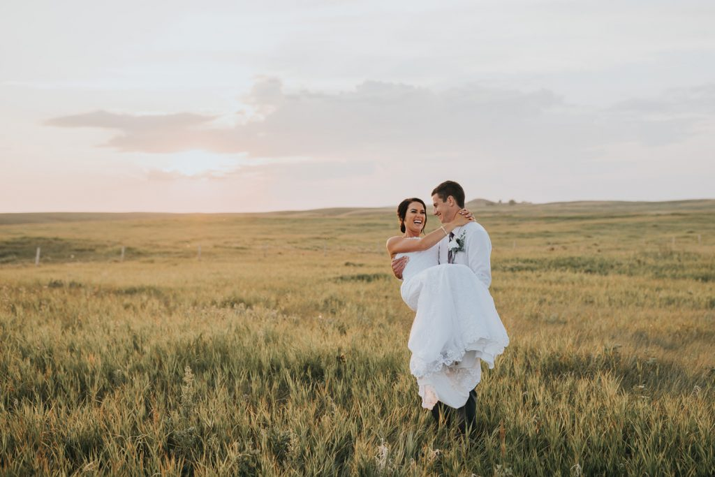 groom carries his bride in a field at sunset cypress hills