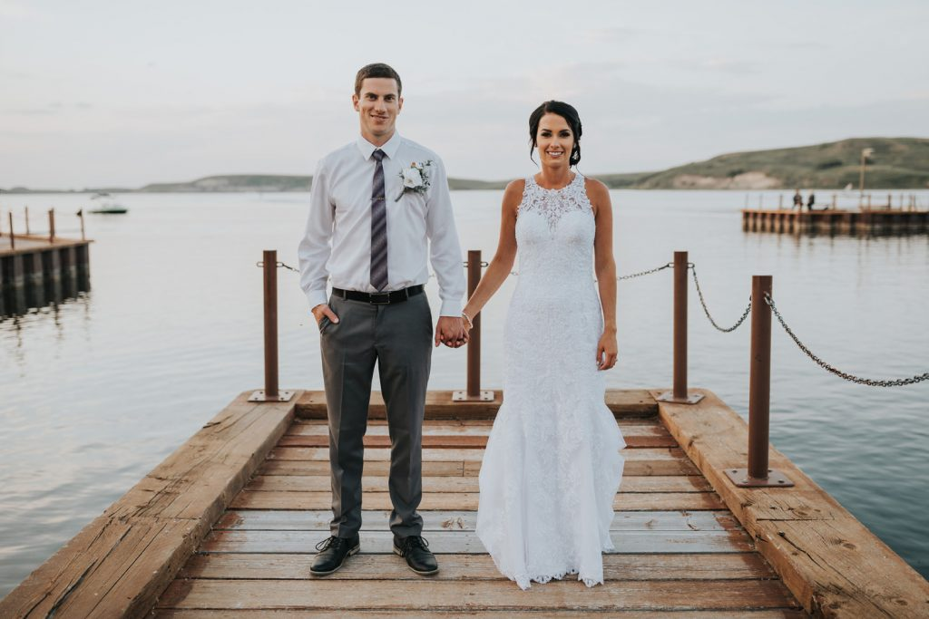 bride and groom hold hands on elkwater lake dock