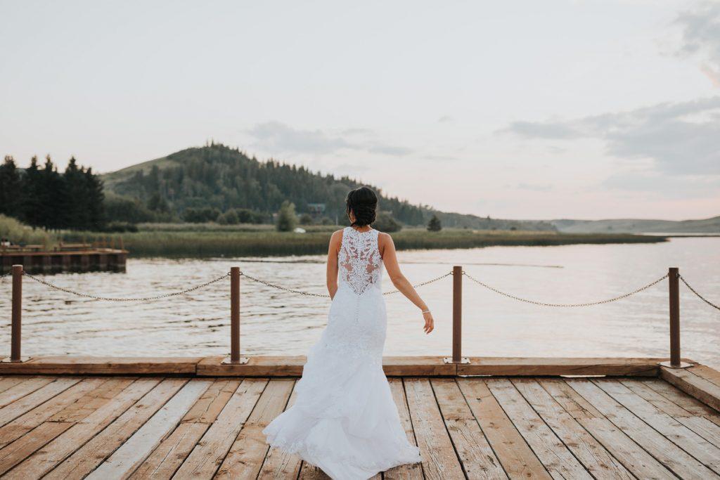 bride dances on dock swaying her wedding dress