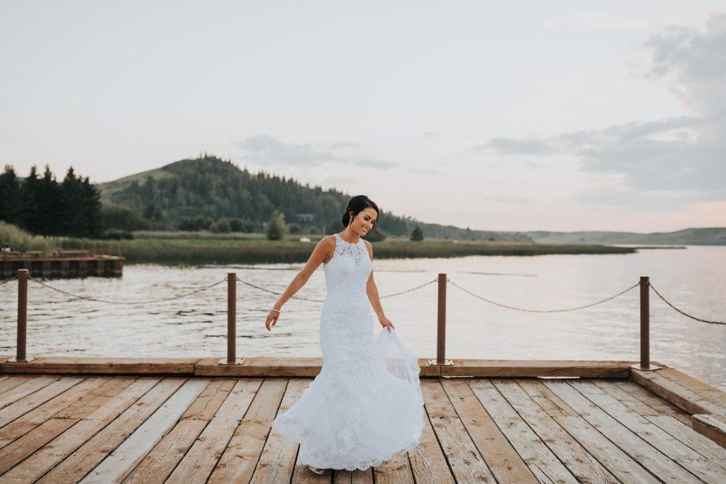 bride dances on the dock twirling her dress