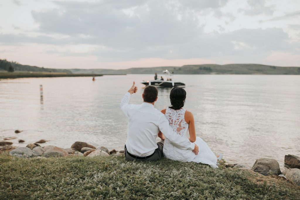 groom gives thumbs up to boat driver during wedding photos