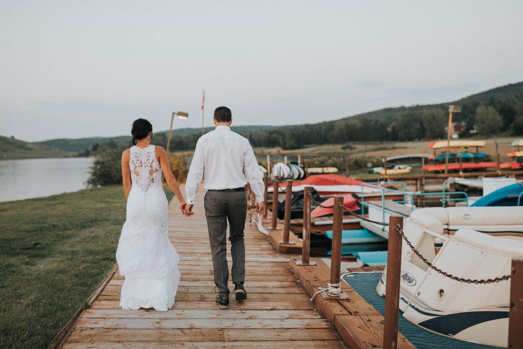 wedding couple walking on boat dock