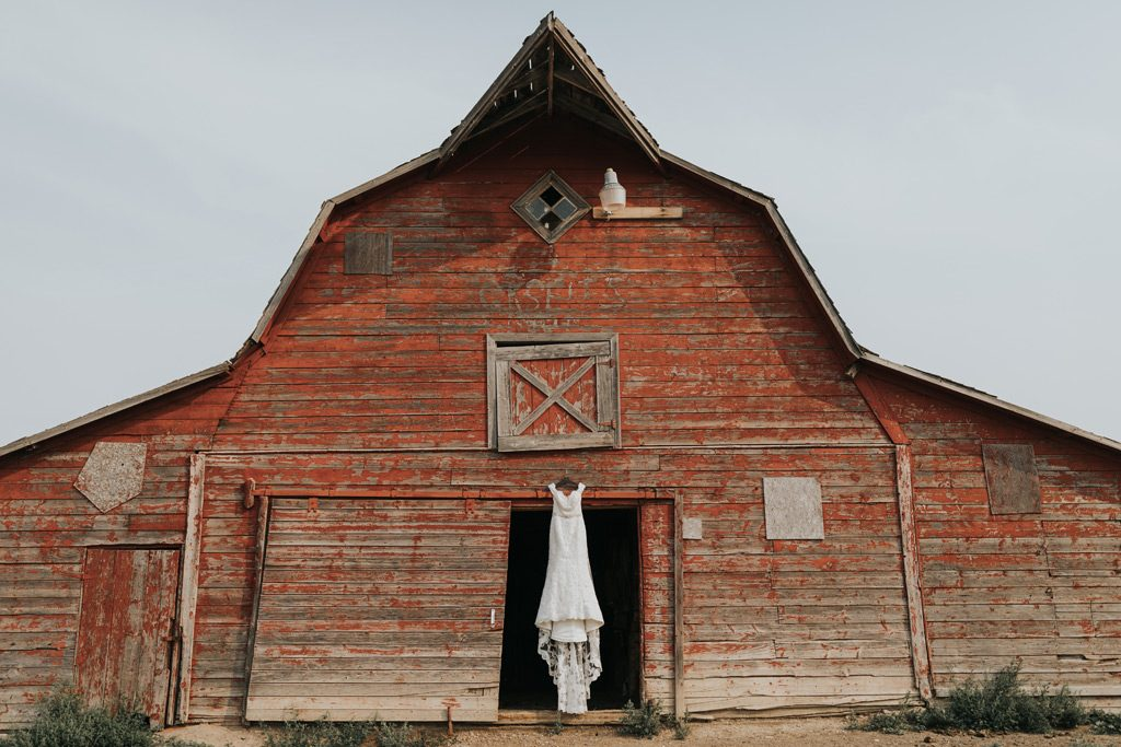 wedding dress hanging in red barn door