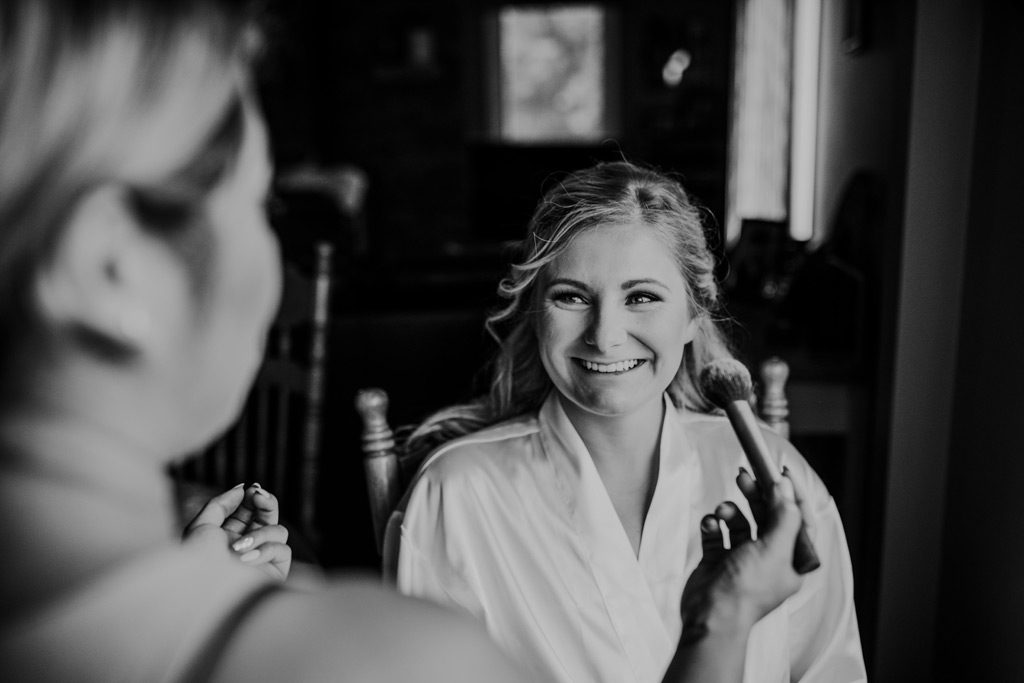 bride smiles getting her makeup done