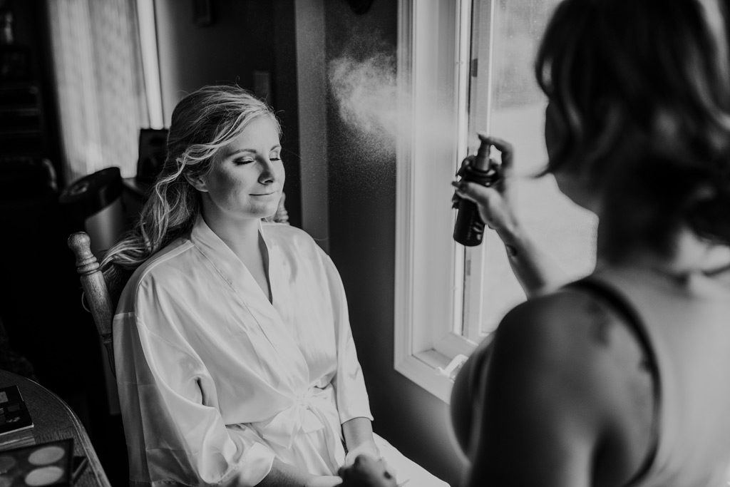 makeup artist sprays setting spray on bride