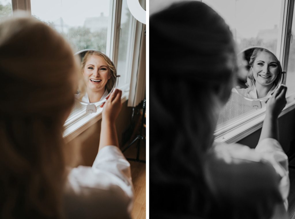 bride smiles happily seeing her hair and map done in mirror reflection