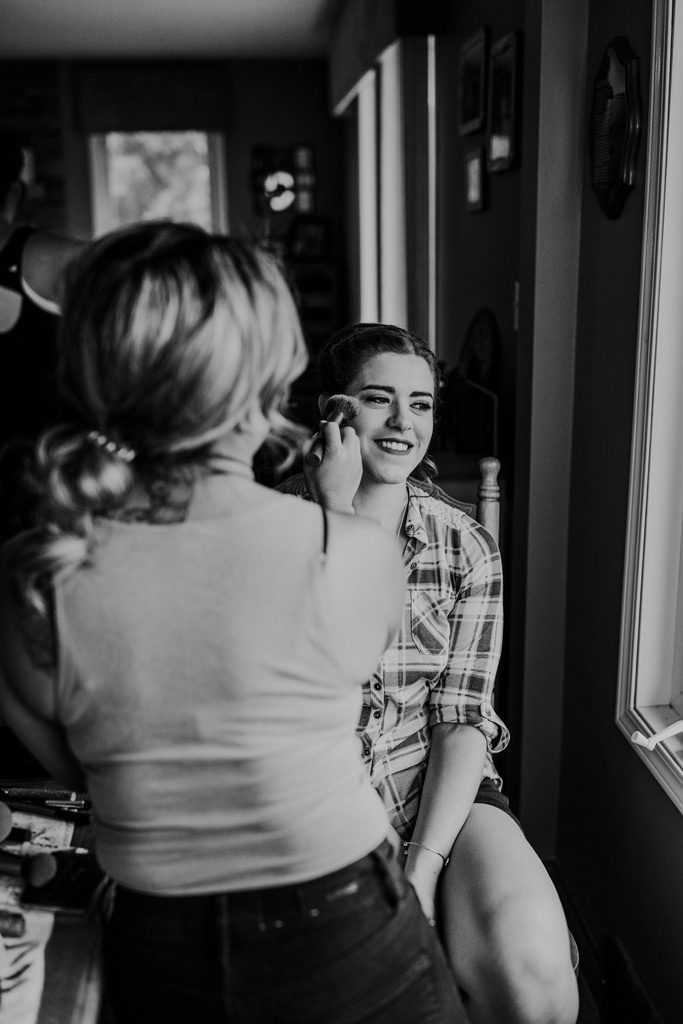 bridesmaid smiles getting makeup done