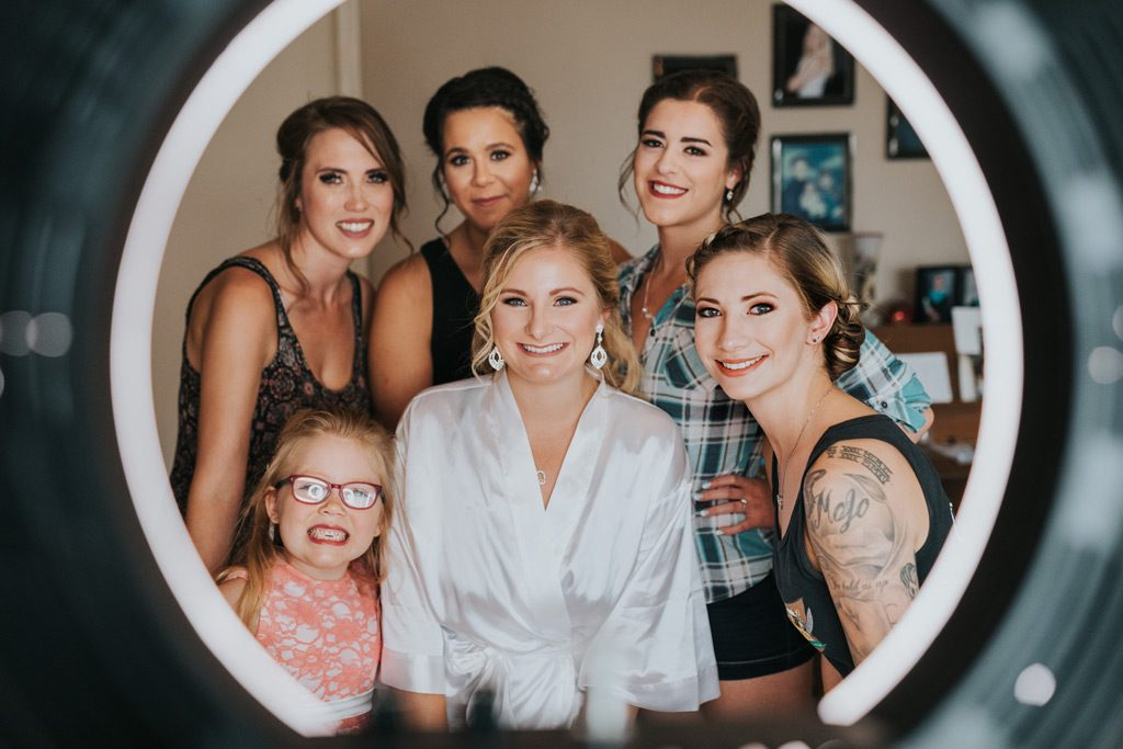 bridal party poses for photo taken through ring light