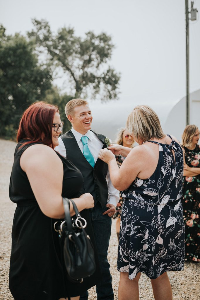 groomsman smiles as he gets his boutonnière on
