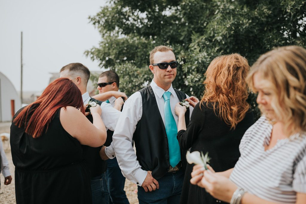 groomsman has help putting on boutonnière