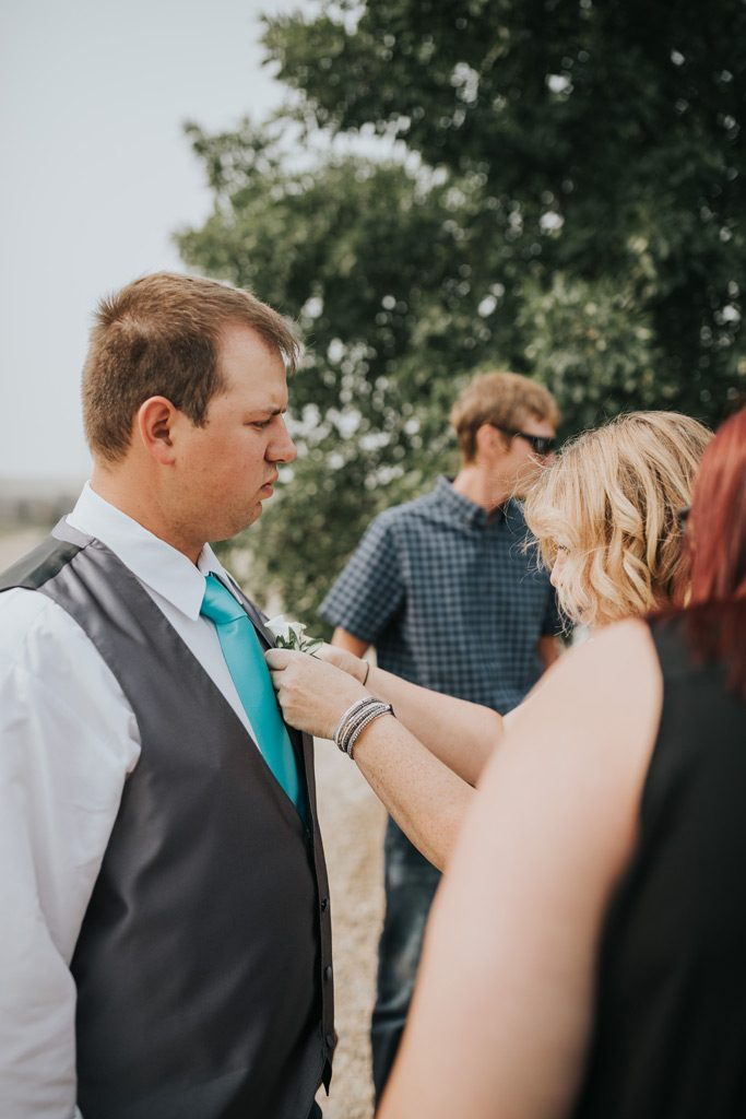 groom has help getting his boutonniere on