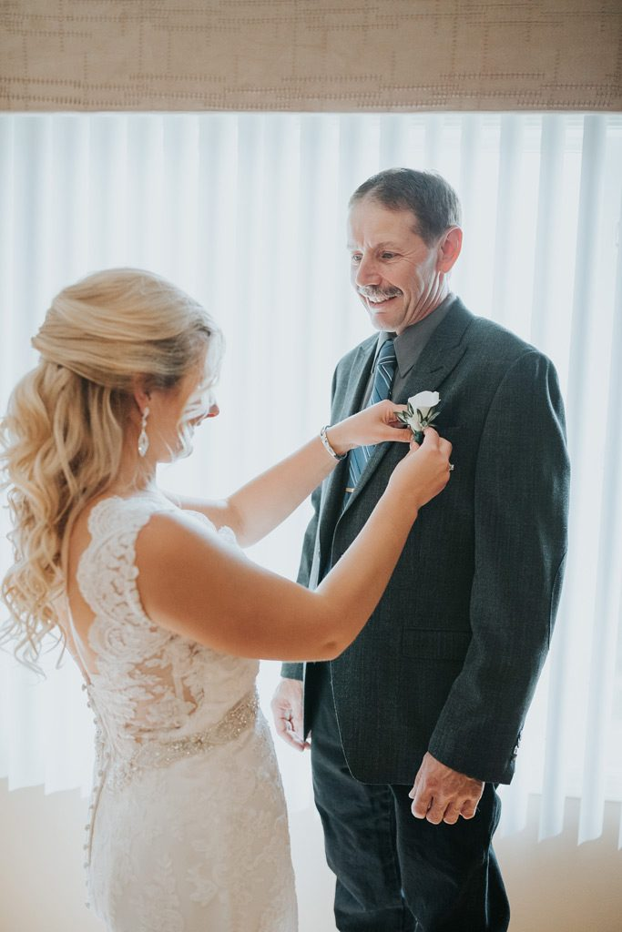 bride putting on her dads boutonniere