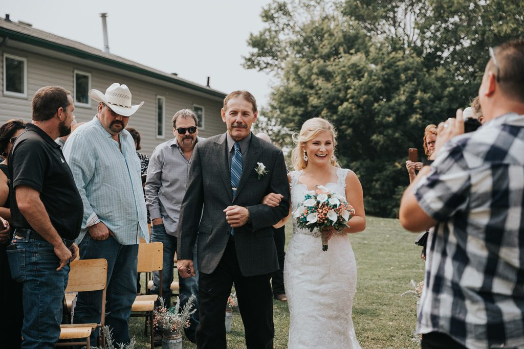 bride smiles big as her dad walks her down the aisle