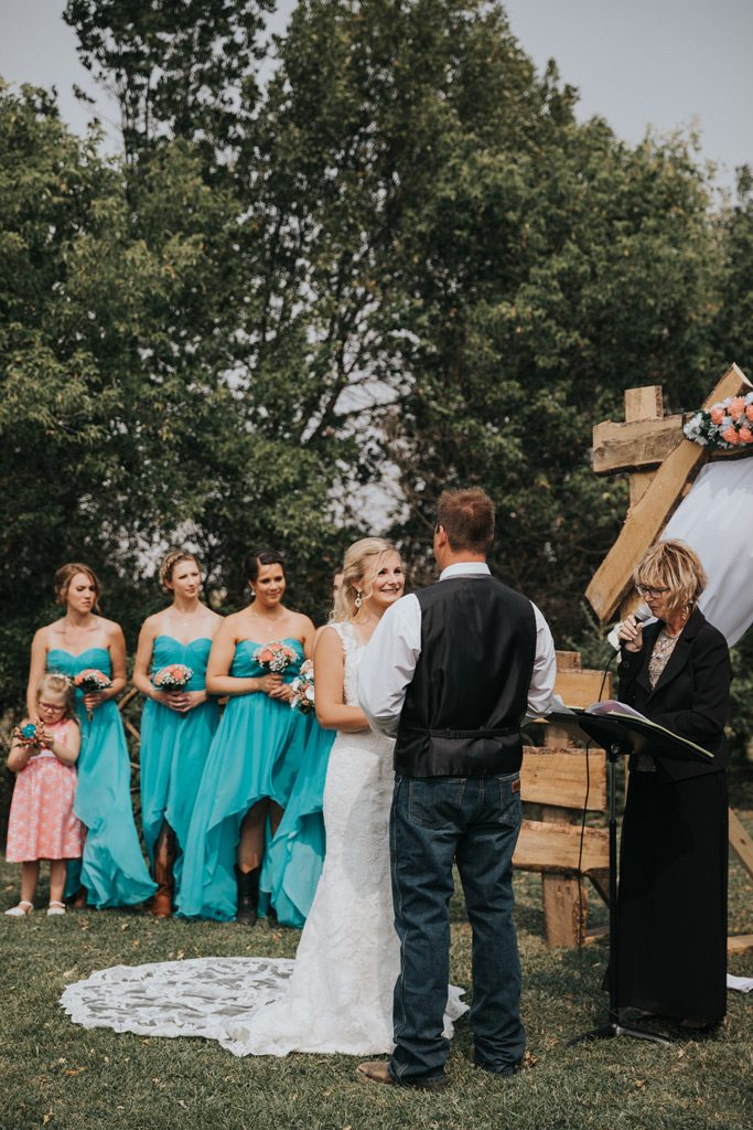 bride smiles as groom says his vows