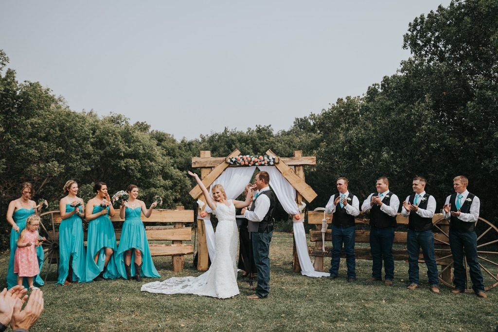 bride throw hands up in celebration during wedding ceremony