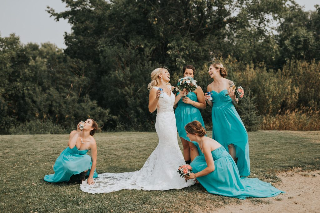 funny bridesmaids photo fixing brides dress drinking beer