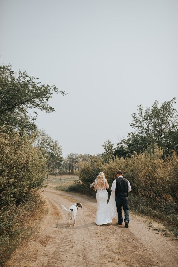 groom holds brides long train walking with their dog