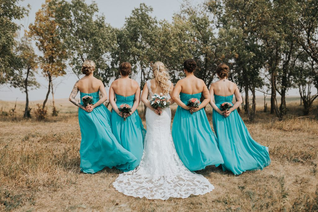 bridesmaids stand with bouquets behind them
