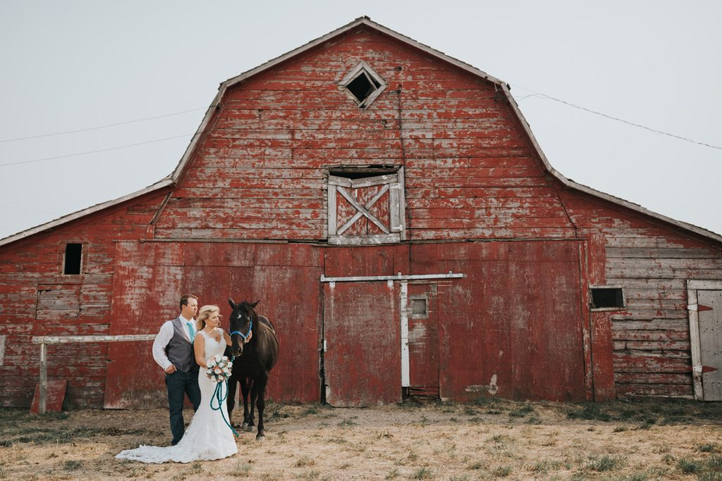 bride and groom stand by barn with her horse
