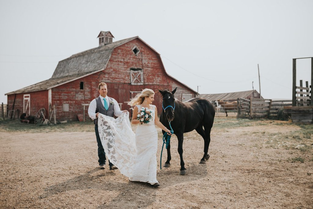 groom holds brides train as she walks with her horse medicine hat stampede royalty