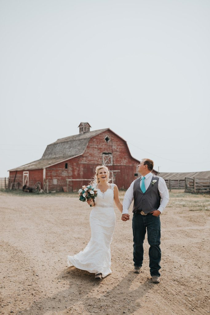 bride laughs walking with groom by red family barn
