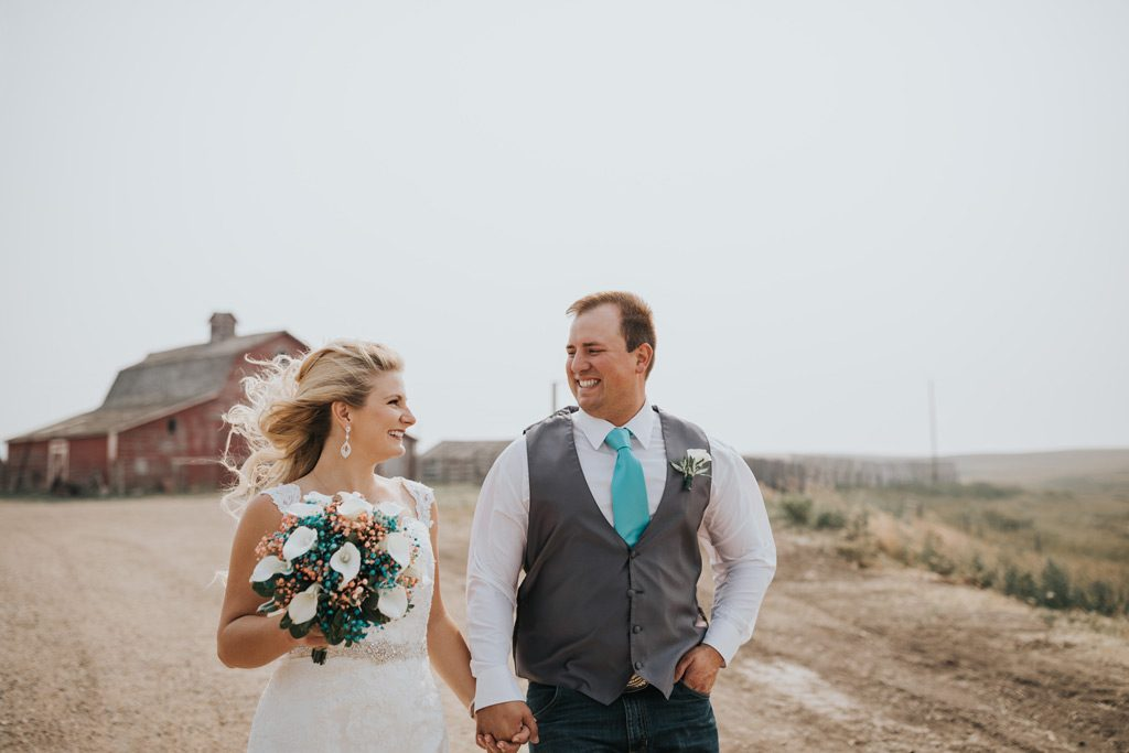 bride and groom smile at each other walking on family farm