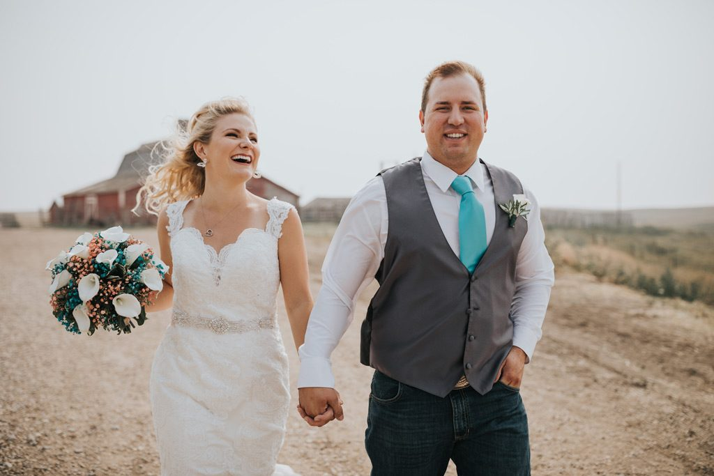 bride and groom laugh running together