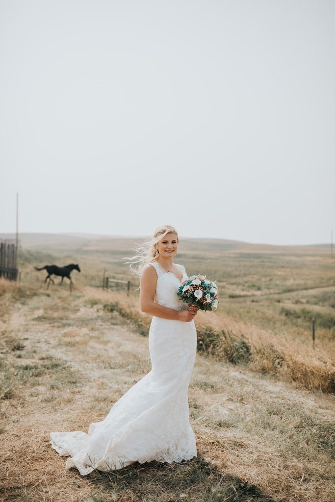 bride stands as her horse runs into field behind her