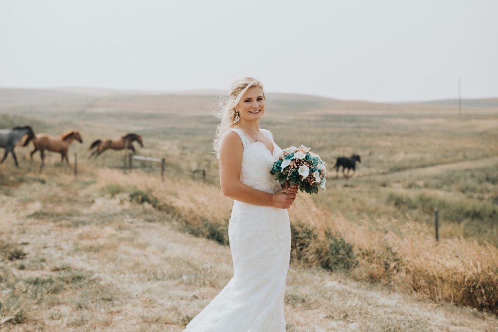 bride stands as horses run into field behind her