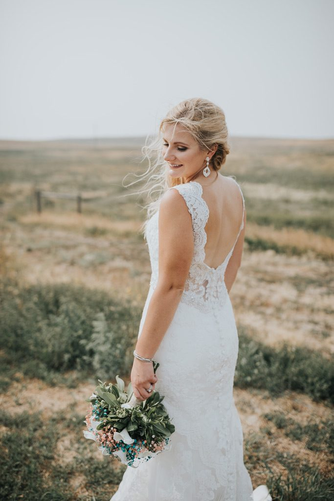 bride stands elegantly with bouquet windy wedding day