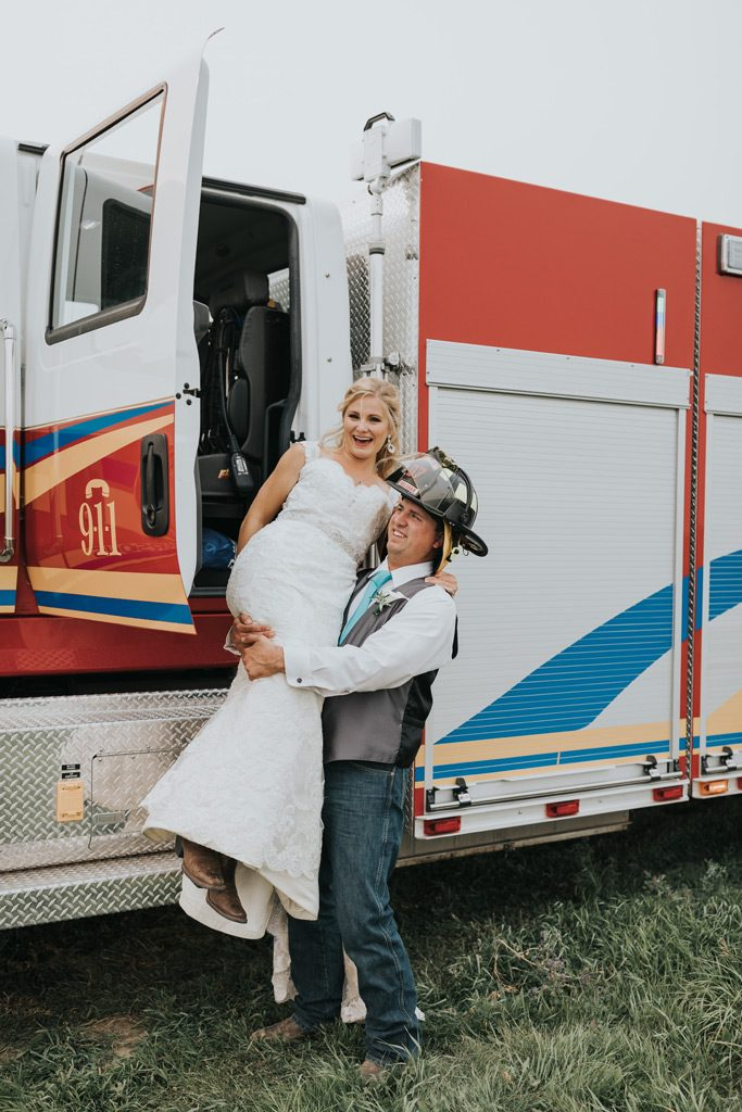 fireman groom carries bride out of firetruck
