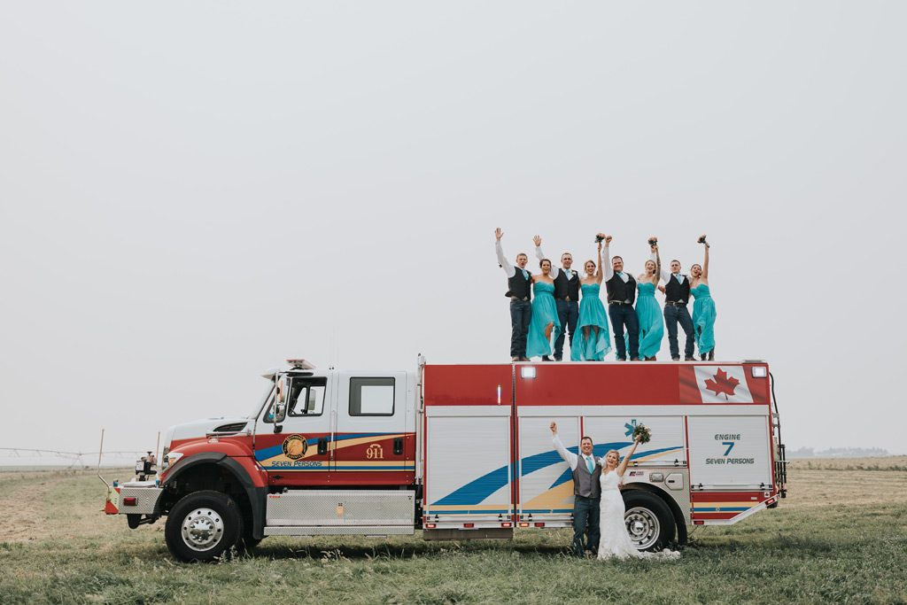 bridal party cheers standing on fire truck