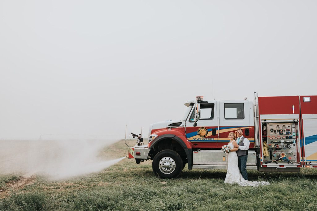 bride and groom stand while fire truck sprays water