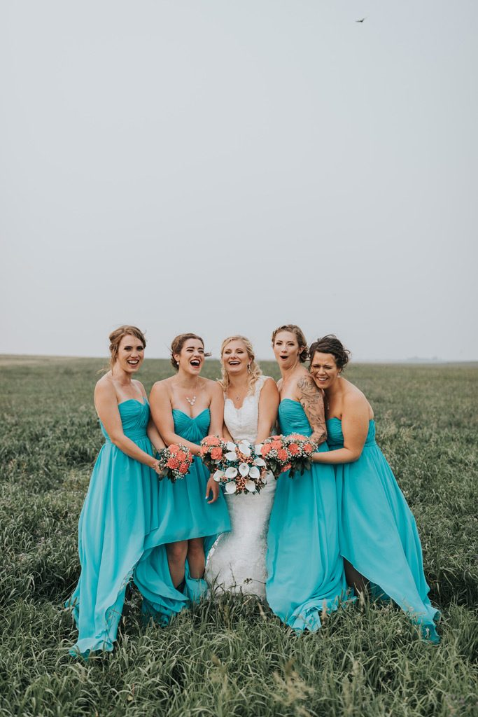 bride with bridesmaids laugh happily farm wedding