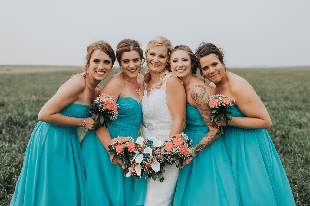 bride poses smiling with bridesmaids seven persons farm wedding