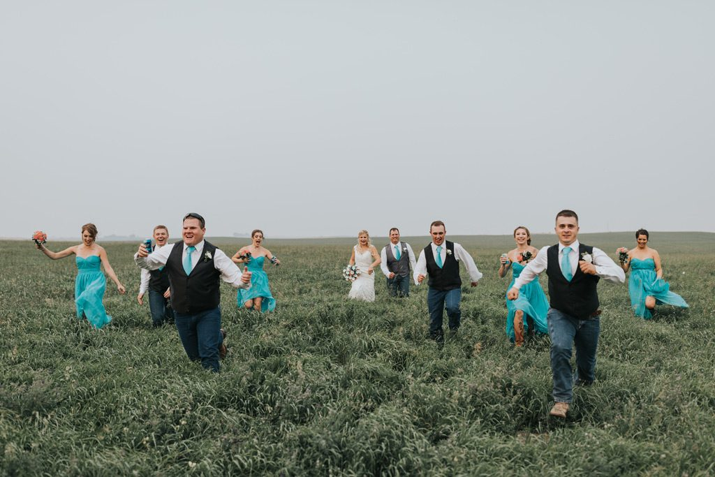 bridal party runs away after photos are finished family farm wedding