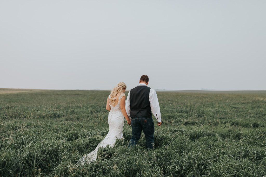bride and groom walking into field together medicine hat alberta