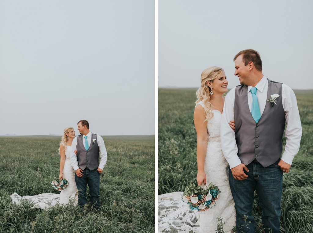 bride and groom stand in filed with tall grass smiling at each other