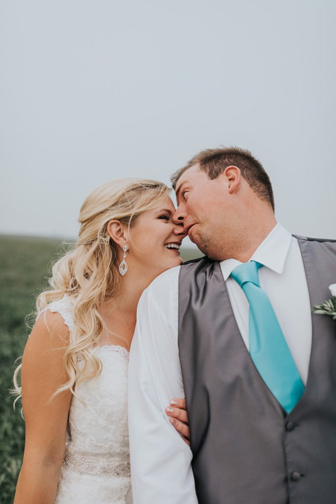 bride laughs as groom makes funny face