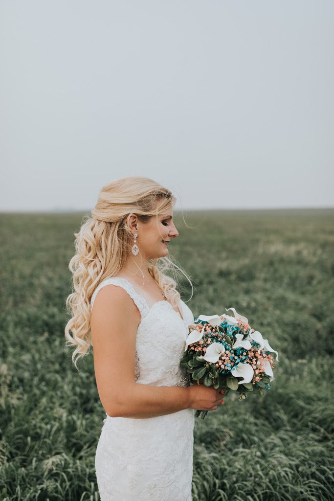 bride poses with bouquet in field