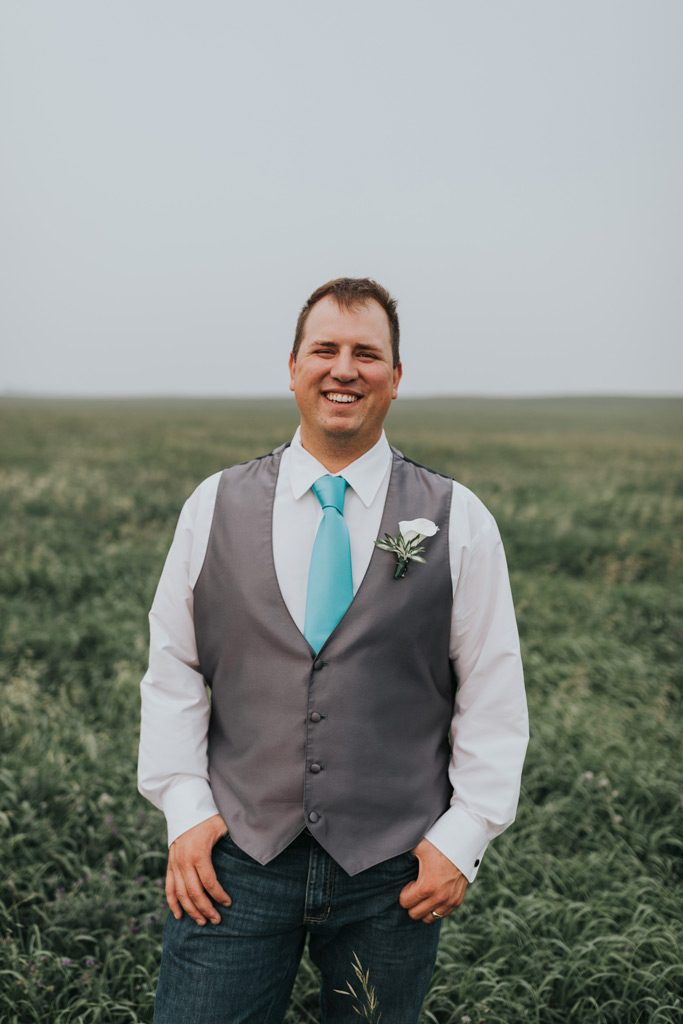 groom smiles standing in field family farm