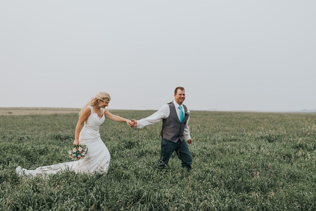 groom leads bride into tall grass field